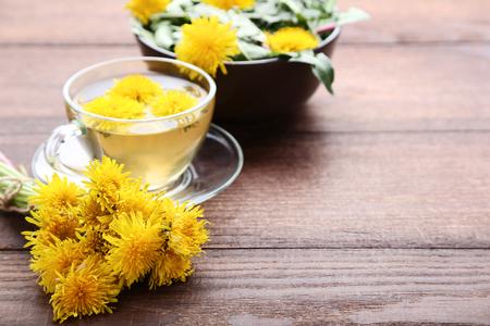 Denti di leone gialli con una tazza di tè sulla tavola di legno marrone Archivio Fotografico