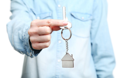 Female's hand holding silver key with house symbol