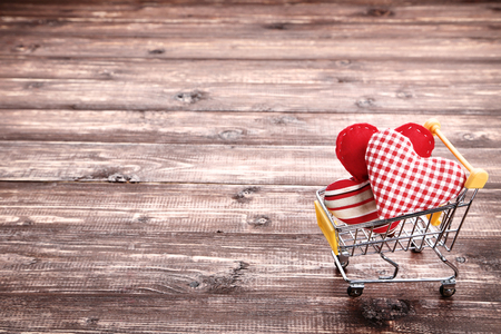Shopping cart with fabric hearts on brown wooden table
