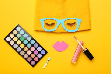 Wimpern mit Papierlippen, Brille und Make-up-Kosmetik auf gelbem Hintergrund. Minimalismus-Konzept
