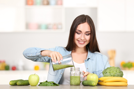 Beautiful woman pouring smoothie in glass jar