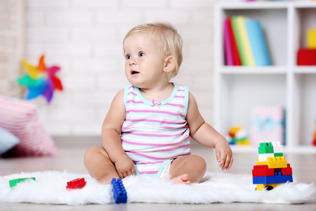 Baby girl sitting on white carpet with toys