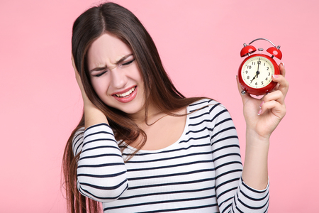 Beautiful young woman with red alarm clock on pink background