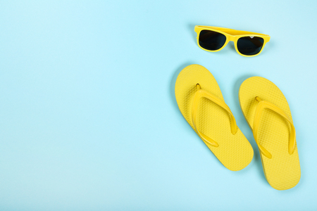 Pair of flip flops with sunglasses on blue background Standard-Bild - 121071815