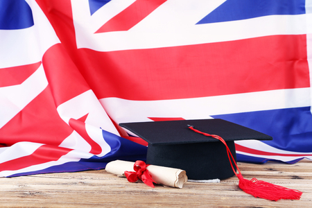 Graduation cap with diploma and British flag on brown wooden table