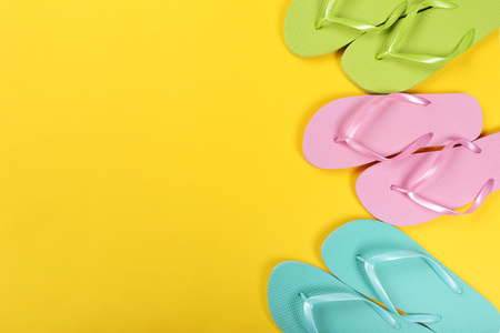 Pairs of colorful flip flops on yellow background