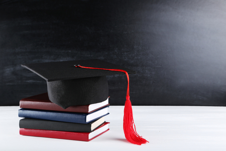 Graduation cap with stack of books on white wooden table 写真素材