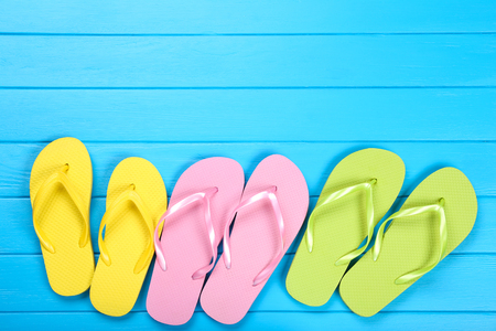 Pairs of colorful flip flops on blue wooden table