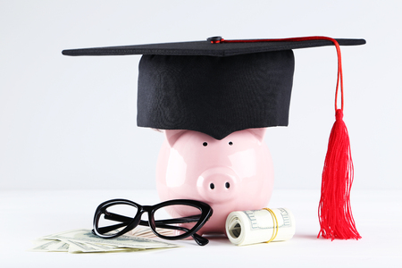 Piggybank with graduation cap, glasses and dollar banknotes on grey background 写真素材