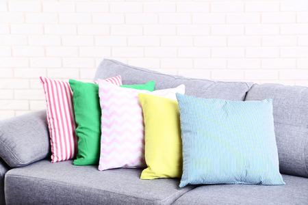 Oreillers moelleux colorés sur canapé gris Banque d'images