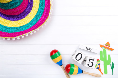 Mexican hat with maracas, cube calendar and paper cactuses on wooden table
