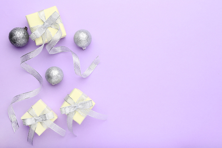 Gift boxes with ribbon and silver baubles on purple background Banque d'images - 121071946