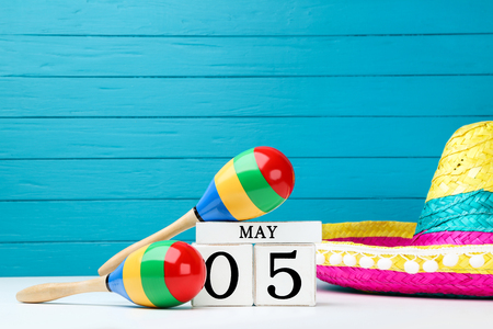Mexican maracas with cube calendar and hat on blue wooden background