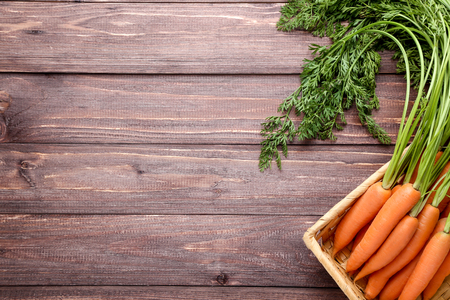 Fresh carrot in basket on wooden background