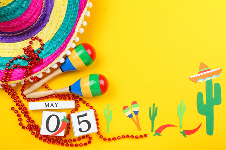 Mexican hat with maracas, cube calendar and paper cactuses on yellow background