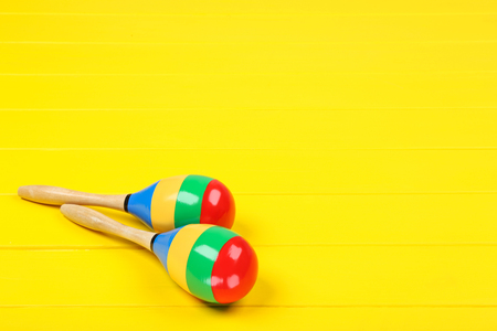 Mexican maracas on yellow wooden table