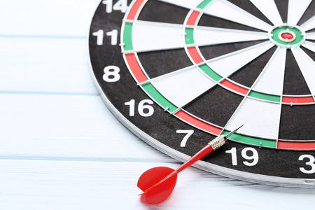 Dartboard with darts on wooden table