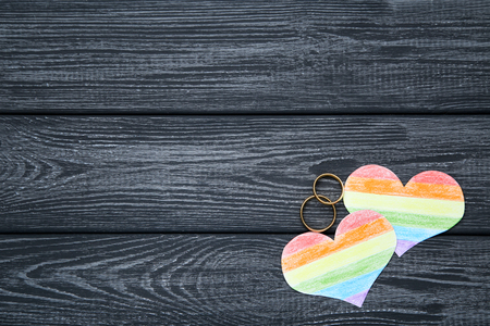 Rainbow paper hearts with golden rings on black wooden table