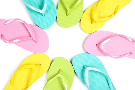 Pairs of colorful flip flops on white background