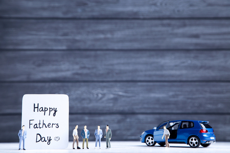 Text Happy Fathers Day with car model and miniature figures on black background