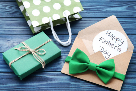 Text Happy Fathers Day with bow tie, gift box and shopping bag on wooden table