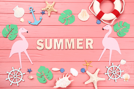Word Summer with seashells, paper leafs and flamingos on wooden table 写真素材