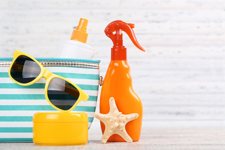 Sunscreen bottles with starfish and sunglasses on white background
