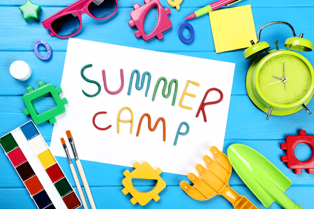 Text Summer camp with plastic toys, sunglasses and paints on blue wooden table 版權商用圖片