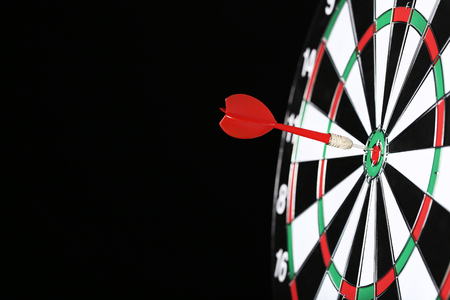 Dartboard with darts on black background