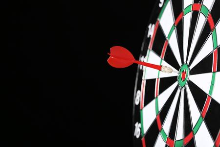 Dartboard with darts on black background