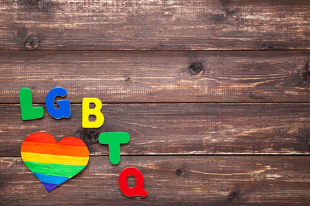Abbreviation LGBT with rainbow heart on brown wooden table Archivio Fotografico