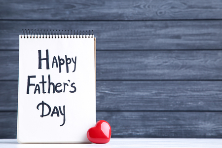 Text Happy Fathers Day with red heart on black background