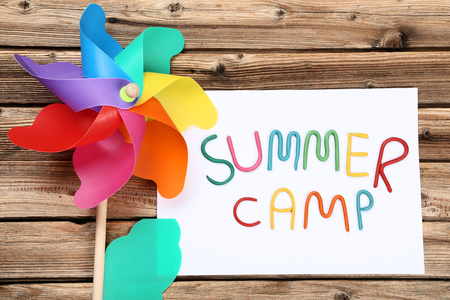 Text Summer camp with windmill on brown wooden table