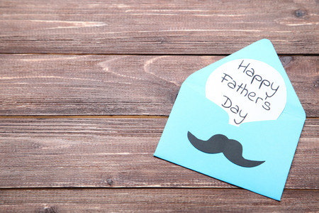 Text Happy Fathers Day with paper envelope and mustache on brown wooden table