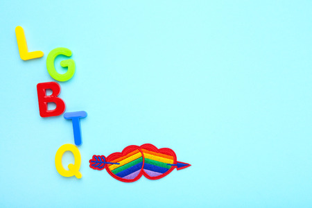 Abbreviation LGBT with rainbow hearts on blue background