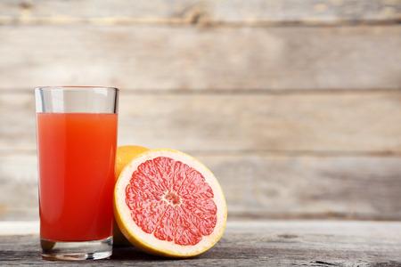 Ripe grapefruits and glass of juice on grey wooden table Reklamní fotografie