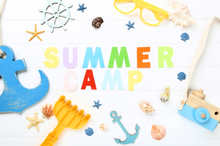 Paper text Summer camp with seashells, glasses and retro camera on white wooden table Imagens
