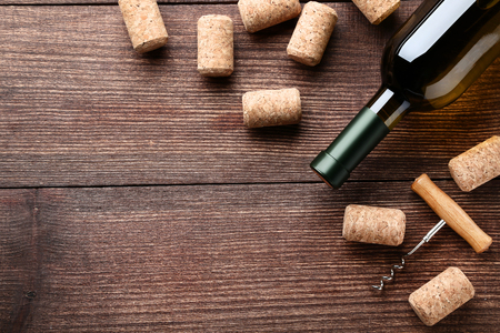 Wine bottle with corks and corkscrew on brown wooden table