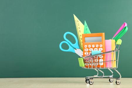 School supplies in shopping cart on chalkboard background