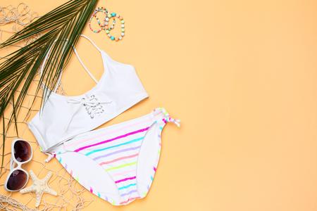 Modezwempak met palmblad, zonnebril en zeester op beige achtergrond