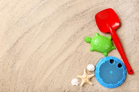 Plastic toys with seashells on beach sand Reklamní fotografie