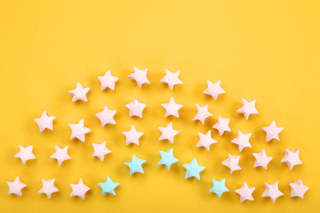 Colorful paper stars on yellow background