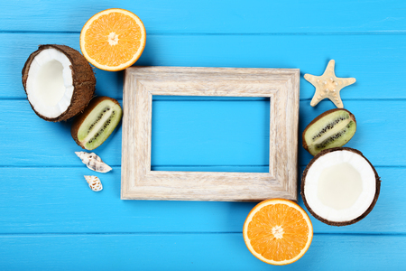 Wooden blank frame with seashells and fruits on blue table