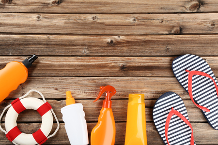 Sunscreen bottles with lifebuoy and flip flops on brown wooden table