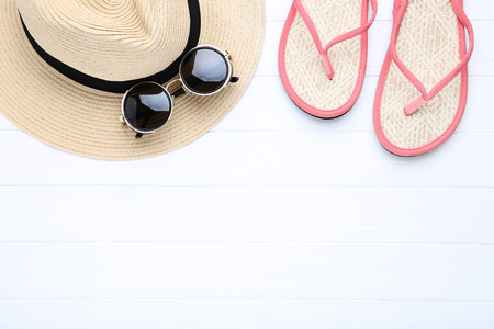 Fashion hat with sunglasses and flip flops on white wooden table 版權商用圖片