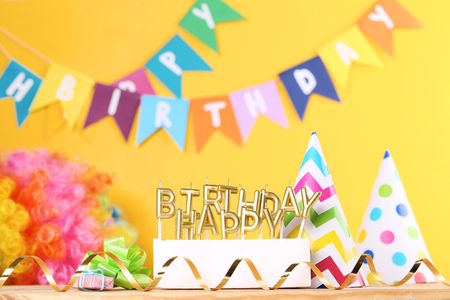 Happy Birthday candles with party decorations on yellow background Banco de Imagens