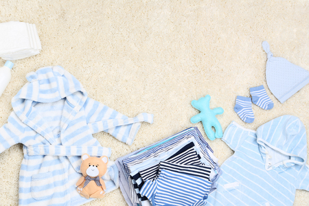 Baby clothes with soft toys and diapers on carpet