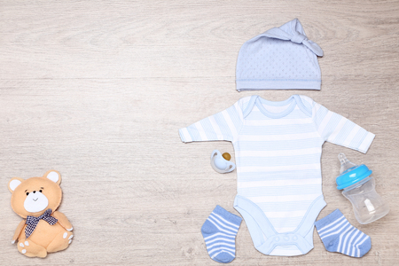 Baby clothes with soft bear toy, soother and bottle on the floor
