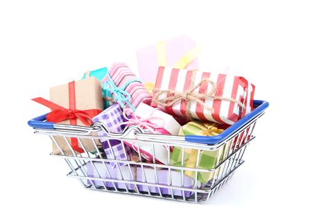 Carrito de la compra pequeño con cajas de regalo aislado sobre fondo blanco.