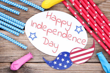 Text Happy Independence Day with straws and rubber balloons on wooden table Imagens